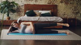 相当怀孕的女孩做着举腿的体育锻炼说谎在瑜伽席子的卧室地板上有顶楼样式室的和 影视素材
