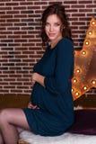 相当怀孕的女孩infront砖墙 库存图片