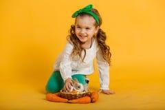 相当愉快的儿童女孩用红萝卜和她的朋友小的五颜六色的兔子,复活节假日概念隔绝在黄色 免版税图库摄影