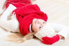 相当愉快的妇女佩带的红色编织了围巾和手套 免版税库存照片