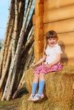 相当愉快的小女孩坐 库存图片