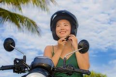 相当愉快的年轻人和调整摩托车在滑行车摩托车的逗人喜爱的亚裔中国妇女盔甲骑马隔绝在蓝天  免版税库存照片