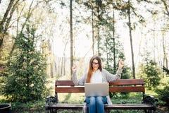 相当成功的妇女用她的被举的手,当研究膝上型计算机,室外在公园长椅时 免版税库存图片