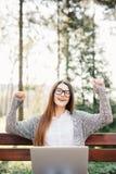 相当成功的妇女用她的被举的手,当研究膝上型计算机,室外在公园长椅时 库存图片
