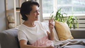 相当成熟夫人谈话,打手势,坐在现代公寓的长沙发 股票视频