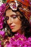 相当成熟妇女外面在桃红色花,秀丽中在埃及植物群特写镜头组成 库存图片