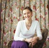 相当成熟妇女愉快微笑的坐在屋子内部,生活里 免版税图库摄影