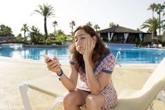 相当拉丁妇女哀伤在她巧妙的电话在度假 库存照片
