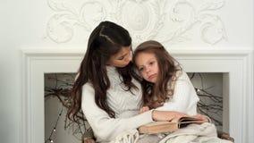 相当拒绝的小女孩与她的妈妈一起读圣诞节传说 免版税库存图片