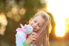 相当拥抱喜爱填充动物玩偶-一只猫的小女孩为 免版税库存图片