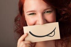 相当拿着与微笑图画的女孩白色卡片 图库摄影
