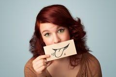 相当拿着与微笑图画的女孩白色卡片 免版税图库摄影