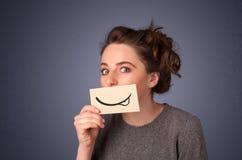 相当拿着与微笑图画的女孩白色卡片 免版税库存照片
