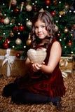 相当拿着圣诞节装饰品的小女孩 图库摄影