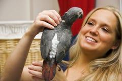 妇女和她的宠物非洲人般的灰色鹦鹉 免版税库存图片