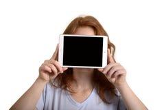 相当拿着微型片剂个人计算机的红发妇女在面孔前 免版税库存图片