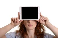 相当拿着微型片剂个人计算机的红发妇女在面孔前 免版税库存照片