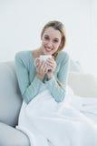 相当拿着杯子的偶然妇女坐长沙发在毯子下 免版税库存照片