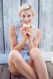 相当拿着杯形蛋糕的白肤金发的妇女 免版税库存照片