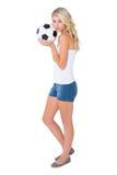 相当拿着球的白肤金发的足球迷 免版税库存图片