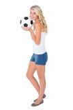 相当拿着球的白肤金发的足球迷 免版税图库摄影
