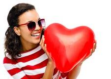 相当拿着红色心脏气球的混合的族种女孩 图库摄影