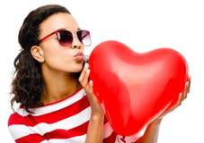 相当拿着红色心脏气球的混合的族种女孩 免版税库存照片