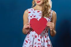 相当拿着红色纸心脏的白肤金发的妇女 免版税库存照片