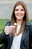 相当提供一朵美丽的花的凉快的女孩 库存图片