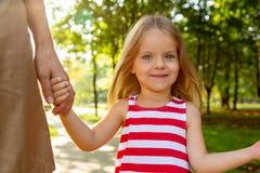 相当握trustingly年轻母亲的手的五颜六色的礼服的小白肤金发的长发儿童女孩特写镜头射击  库存照片