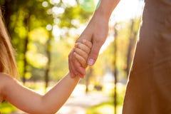相当握trustingly年轻母亲的手的五颜六色的礼服的小白肤金发的长发儿童女孩特写镜头射击  免版税库存图片