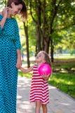 相当握trustingly年轻母亲的手的五颜六色的礼服的小白肤金发的长发儿童女孩特写镜头射击  图库摄影