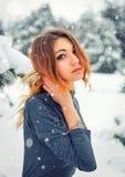 相当摆在多雪的冬天的女孩在冷的森林里 免版税图库摄影