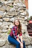 相当摆在对石墙的年轻亭亭玉立的妇女 免版税图库摄影