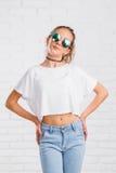 相当摆在白色砖墙上的年轻性感的时尚妇女 库存照片