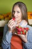 相当摆在的少妇,当吃草莓时 免版税库存照片