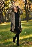 相当摆在秋天公园的典雅的外套的年轻人微笑的白肤金发的妇女 免版税库存图片