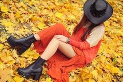 相当摆在秋天公园,皮革帽子的少妇 免版税库存照片