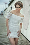 相当摆在鞋带白色的礼服的华美的典雅的性感的少妇 免版税库存照片