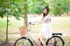 相当放松与自行车的少妇在公园 免版税库存图片
