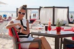 相当放松在海滩餐馆的少妇 库存照片