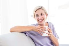 相当放松在长沙发和拿着杯子的白肤金发的妇女 库存照片