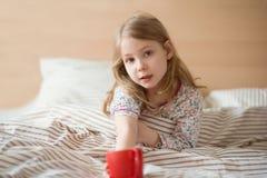 相当放置在床饮料茶的病的小孩女孩 免版税库存照片