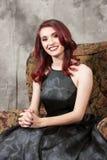 相当斜倚在椅子的棕色目的红头发人女孩 库存照片