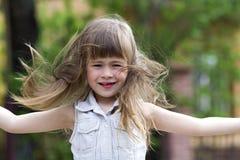 相当无袖的白色礼服的小学龄前女孩有风、滑稽的无牙的微笑和spr吹的美丽的长的金发的 免版税库存照片