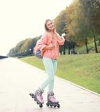 相当时髦的微笑的路辗女孩在城市 免版税库存照片