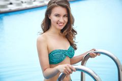 相当明亮的夏天比基尼泳装的少妇在水池附近 库存照片