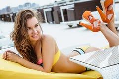 相当明亮的夏天比基尼泳装的少妇在海滩懒人 库存照片