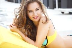 相当明亮的夏天比基尼泳装的少妇在海滩懒人 免版税图库摄影