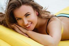 相当明亮的夏天比基尼泳装的少妇在海滩懒人 图库摄影